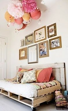 I love everything about this:  The decorated globes hanging from the ceiling, the pictures on the wall, the packing crate daybed!