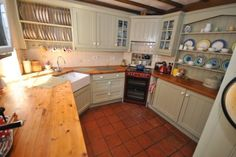 Charming & practical country kitchen with wood counters, quarry tile floor, open plate racks, corner stove & sink, exposed beams - very workable layout - Halse, Somerset, April '15