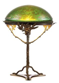 Bohemian glass and brass table lamp, circa 1900, the shade of clear green glass with a purple-gold iridescent layer in the manner of Loetz, supported by a brass tree-shaped base on tripod stand with a single light fixture height 45 cm, diameter 35 cm