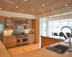 The polished hardwood floor in this contemporary kitchen mirrors the sleek wood ceiling above. Recessed lighting adds to the natural light filling the neutral space, which is open on three sides. Stainless steel appliances are housed along the kitchen's single full wall.