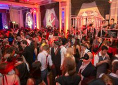 Busy dancefloor with masked guests, drinking and dancing