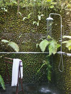 rustic outdoor shower - tropical outdoor shower in the corner of a stone-walled patio in Bali - elleuk.com via Atticmag