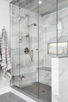 Polished nickel towel hooks are mounted beside a seamless glass steam shower featuring a lighted niche framed by gray and white marble wall tiles and positioned above a tiled bench with a gray quartz top.