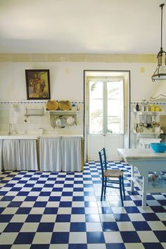 Whitewashed walls and ivory tiles in the kitchen, with shelves to display ceramic pots and dishes from Lucia Guarini's line, L'Ocra. (Photo: Ricardo Labougle)