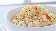 COCONUT RICE 2 cups long grain rice 1 tsp crushed fresh ginger 1 small onion, finely chopped 3 cloves garlic crushed 1 Thai chili finely chopped 3 scallions (spring onions) finely chopped ½ cup toasted coconut flakes 2 ½ cups chicken stock 1 cup coconut milk 1 tbsp canola oil Salt to taste