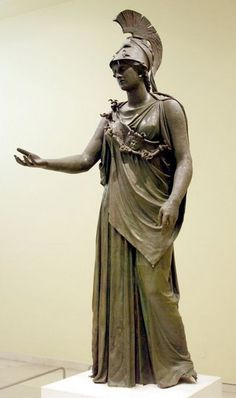 """4th C. B.C.E. Athena of Piraeus"""" over life-size bronze statue wearing a heavy Peplos and Corintinian helmet is a power image Yet- Her gentle expression, her relaxed contrapposto stance and extended arm shows a new air of approachability not seen in the archaic period. Classical period, Greece"""