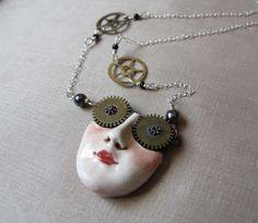 A pair of vintage watch gears form the eyes / sunglasses on this unusual pendant. The face is porcelain and has been created from wet clay and fired