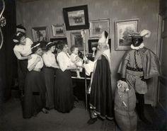""". Sinterklaas . Zwart Piet bewaakt de zak met strenge blik."""" 1911."""