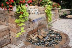 This soothing water feature built with VERSA-LOK flows right into the paver patio, where the water recirculates.