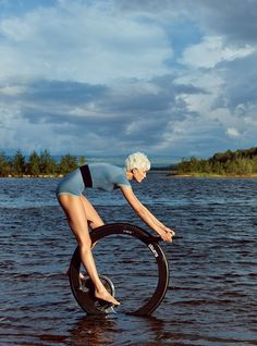 Spin Cycle - Kloss on Ciclotte's stationary exercise bike in the Lule River, where hotel guests kayak, swim, and fish. Jason Wu scubasuit. Christy Rilling Studio elastic belt. In this story: hair, Julien d'Ys for Julien d'Ys; makeup, Dick Page for Shiseido. Produced by Day Stockholm.
