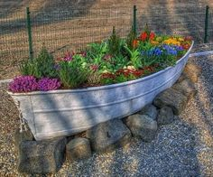 Garden- Old Boat Garden! Love this with the field rock around the bottom! Putting this in front of the house and adding our house number