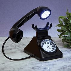 """Telephone Alarm Clock Lamp, $19.99, Item 47363.    Our retro-style rotary telephone has a bright 12 LED lamp in the earpiece. It's easy to adjust with the flexible metal cord. Lamp has an on-off switch on the handle. Clock face has glow-in-the-dark hands. Alarm lights up the clockface with a small LED. Measures 8"""" long x 6"""" deep x 5½"""" tall."""
