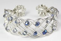 Stunning cuff bracelet made from 1mm sterling silver wire and 6mm rondelle crystal beads in a gorgeous blue/purple colour. The 10 strands of silver wire are woven into an open, flowing design and finished with spiralled ends. By Jayne at Woven Art Jewellery. www.wovenartjewellery.co.uk