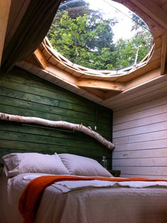 Bedroom with green wood clad walls and a round window / skylight above the bed. What a wonderful view to gaze up at...