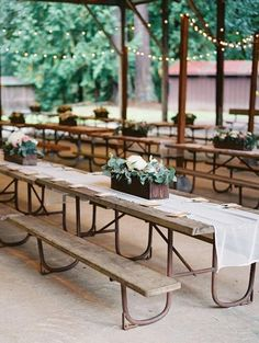 Casual sheer white table runners with low arrangements in wooden containers add simple elegance to a picnic shelter.