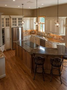 See the traditional kitchen equipped with a large maple island, oak floors and a travertine backsplash on HGTV.