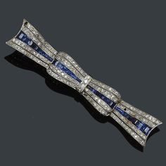 An early 20th century sapphire and diamond bow brooch  The ribbon design set throughout with single-cut diamonds, with central row of calibre sapphires, (two vacant settings, diamonds included with the brooch), two colour precious metal setting, length 8cm.