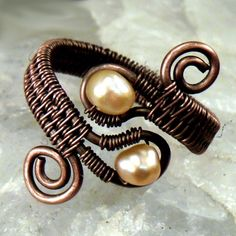 Learn to create a bold, classic-looking ring using basic wire work and wireweaving skills with this tutorial from Wynter Creations. This design includes a number of beginning and intermediate wire work techniques, including forming a frame and spirals, weaving with three base wires, and wrapping drilled beads into a frame. This is an ideal project for the advanced beginner - the crafter who's had some experience with wire and wants to learn more.