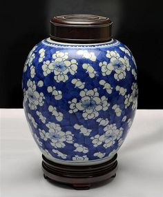 A BLUE AND WHITE GINGER JAR QING DYNASTY, KANGXI PERIOD painted on the exterior in bright cobalt blue with scattered flower heads reserved on a 'cracked-ice' ground, wood cover and stand (3)  22.5CM