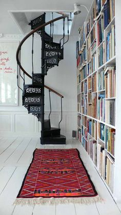 Bookshelf, white floor, black stairs and a red/orange rug