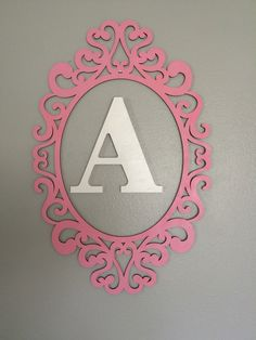 DIY Wooden laser cut frame painted baby pink & Wooden Letter painted white; both from Michael's----For Baby Girl Nursery