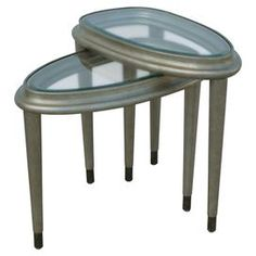 Two glass top nesting tables with brass-tipped legs.  Product: Small and large nesting tablesConstruction Material: Metal and glassColor: Silvery goldFeatures:  Oval shapeBeveled glass tops and brass tips on legs Dimensions: Small: 21.25 H x 24 W x 14.5 DLarge: 24 H x 24 W x 14.5 D