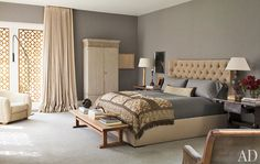 In the master bedroom, a custom-made bed is upholstered in a HOLLY HUNT Great Plains fabric and topped with an antique French textile from Lief; the Torpedo floor lamp is by Jane Hallworth, the cabinet is a Gustavian antique, the walls are upholstered in gray flannel by Holland & Sherry, and the nightstand on the right is a 17th-century Tuscan table from Richard Shapiro Antiques and Works of Art