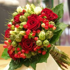 A green and red bouquet for the bride. Made out of red roses, closed white rose buds and red berries