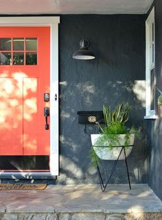 """Glidden """"Orange Tiger Lily"""" paired with Behr """"Evening Hush"""" give this little bungalow some major curb appeal. Light fixture by Rejuvenation."""