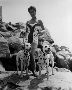 1955:  Joan Smith wearing a spotty swimsuit and with two dalmatians on leads.