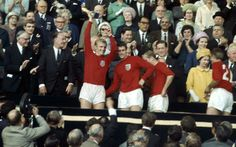 30 July 1966: Captain Bobby Moore holds the Jules Rimet trophy aloft following England's 4 -2 victory over West Germany in the the World Cup Final at Wembley Stadium. Geoff Hurst stands next to him, while Roger Hunt speaks to the Queen.  Picture: Fox Photos/Hulton Archive/Getty Images