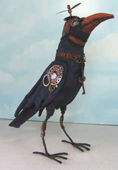 """Steampunk Crow  by Frowning Frances Folk Art.   This wonderful pattern makes a 10"""" crow.  The body of the crow will be made from painted muslin. The legs are wire.  The cap is made from fabric and twill tape, painted to look like leather.  A propeller charm completes the hat but you can add as many charms, gears and found objects as you want!"""