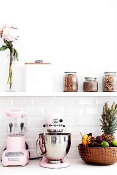 Kitchen with white wall, white tile back-splash, pink KitchenAid accessories, brass bowl with fruit, white shelves, glass vase with flowers, and glass jars for baking supplies