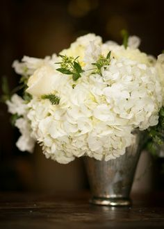 white hydrangeas and roses in a mint julep cup