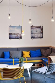 A custom sofa, supported by wooden pallets, was inspired by the area's fruit industry; the three tiers of cushions are strapped down, as if prepared for shipping. Hee Lounge Chairs by Hay provides extra seating and Muuto E27 pendant lights hang from the ceiling.