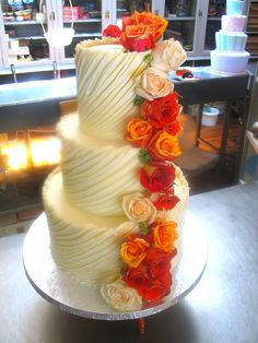 3-tier Wicked Chocolate wedding cake iced in spanish textured white ganache decorated with fresh cream & burnt orange roses