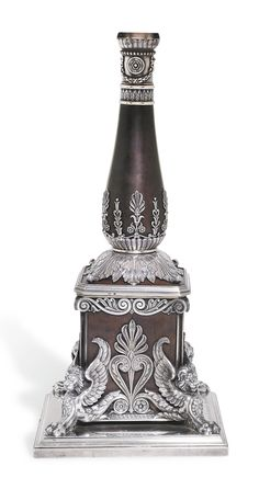 A Fabergé silver-mounted wood lamp, workmaster Hjalmar Armfelt, St Petersburg, 1899-1908. The amaranth plinth supported by silver winged lions and mounted with anthemia, the baluster form stem rising from acanthus leaves with further neo-Classical mounts, the collar with leaf tip border and bound laurel swags, the silver base with engraved inscription in Russian 'To Baron E. Iu. Nolde from the Office of the Committee of Ministers'. (Baron Emmanuel Iulievich Nolde)