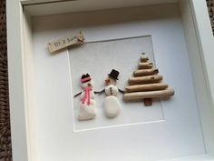 A pebble snowman and snowlady stand beside a driftwood tree. Let it snow.quote makes this a lovely and unique picture to give or pop up on your own wall in the festive period. In a 10 x 10 white box frame with a glass front. Christmas Pebble Art, Christmas Art, Handmade Christmas, Christmas Decorations, Christmas Ornaments, Christmas Frames, Christmas Pictures, Stall Decorations, 12 Days Of Xmas