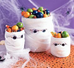 Home Spooky Home: Mummies Love Candy  Make a spooky candy dish with plastic water bottles, gauze, and googly eyes.