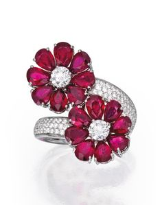 PLATINUM, RUBY AND DIAMOND RING Of floral and crossover design, set with 16 pear-shaped rubies weighing approximately 8.20 carats, the flowerheads centered by two round diamonds weighing approximately .85 carat, within a mounting accented by small round diamonds weighing approximately 1.25 carats