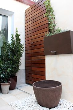 Puerta de madera de IPE en patio que oculta la maquinaria del AA y los cuadros de instalaciones #jardines #madera