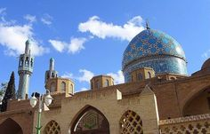 Tiled dome and minarets, with cupolas, of the adobe Shrine of Shah Nematollah Vali — in Mahan, Kerman province, southern Iran.