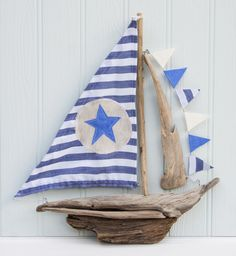 Beautiful New England style inspired and hand-crafted driftwood boat, with fresh coloured blue and cream striped sails and a large blue star. Description from coastalhome.co.uk. I searched for this on bing.com/images