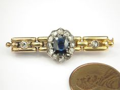 ANTIQUE AUSTRO HUNGARIAN 14K GOLD SAPPHIRE & ROSE CUT DIAMOND BAR BROOCH c1890  A fine quality antique Austro Hungarian, solid 14 carat gold (tests thereabouts) brooch; with chain-link styled frame and set with glistening rose-cut diamonds in silver topped settings surrounding a vibrant natural rich blue sapphire.