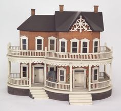 "Seaside Cottage – American, ca.1890. An endearing small folk-art house featuring a delightfully detailed wrap-around curving two-story porch. Exterior decorated with lithographed brick paper, carved decorative barge-board, and a textured, sand-painted base. Roof has three paper covered chimneys. Accessed from the back, the interior has original over-scaled wallpapers, unfurnished, 19.5"" t, 24"" w, 15"" d."