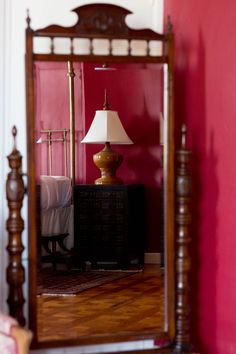 Large mirror in red bed room, with reflection of antique Chinese cabinet and four poster bed www.chateaurobertfrance.fr