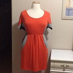 """Orange color block dress with pockets Orange with grey and black side color block. Short sleeves, elastic waist and pockets. Measures approx. 35"""" from shoulder to hem, laying flat 17"""" across chest. 67% polyester 29% rayon 4% spandex. Best fits size 12 Delirious Dresses"""