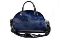 """A questa borsa è stato dato il nome di Cappelliera per la sua forma che richiama le cappelliere di un tempo, valigie, baulotti, dove venivano riposti i cappelli di dame e cavalieri per i viaggi. Particolarmente capiente è sicuramente un modello di borsa """"must  have"""" che non può mancare nell'armadio anche come bagaglio a mano o beauty-case. In questa versione la pelle tipo cavallino blu tinta unita è accostata a quella nera martinica.http://www.modaiole.it/categoria/borse-in-pelle/cappelliere"""