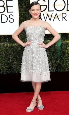 MILLIE BOBBY BROWN   accents her Jenny Packham champagne sequin fringe dress with illusion neckline and equally pailette-adorned silver Sophia Webster kitten heels.