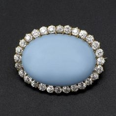 PERSIAN TURQUOISE AND DIAMOND BROOCH 18k yg with oval cabochon turquoise of robin's egg blue surrounded by twenty-eight OEC diamonds, approx. 2 cts. TW, ca. 1900. 12.2 gs. GW. 1'' x 1 1/4''